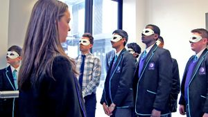 Seven teenage boys are standing together at the bottom of a school stairway, looking up, wearing white masks covering their eyes. A girl without a mask is standing across from them, looking toward them.