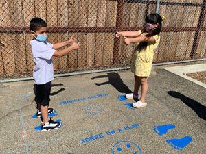 Elementary children standing on painted asphalt of school playground