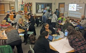 A group of educators are sitting at classroom tables collaborating.