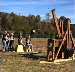 Teens are outside on a field catapulting pumpkins from a wooden contraption.