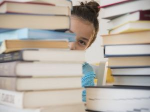 Student behind a pile of books