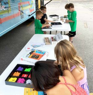Young kids are making things with electronic building blocks at two pop-up tables beside a bus.