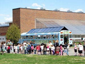 Students line up beside a blue bus with a glass roof.