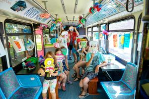 A group of kids and adults are sitting in a bus, holding Halloween masks they created.