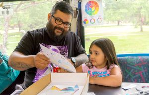 A father and daughter are making art on a bus with paper and markers.