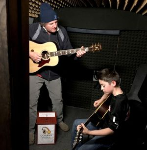 A man and a teenage boy are recording themselves playing guitar inside of a bus.