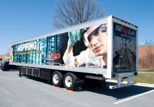 The exterior of a semi-truck with a picture of a boy in a lab coat wearing protective glasses and gloves.