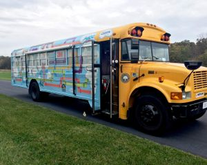 A side exterior shot of a school bus. The majority of the bus is painted blue with colorful piping and white clouds.