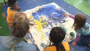 Three young students and a teacher are kneeling on a blue tarp in class pouring paint onto a large canvas.