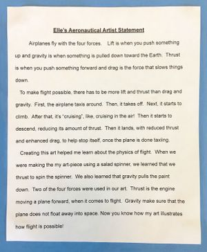 A second-grade student's typed artist statement glued against blue construction paper explaining the four forces of flight -- lift, gravity, drag, and thrust -- and how making art with a salad spinner used two of the forces.