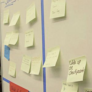 Post-it notes with academic goals written on them posted on a whiteboard.