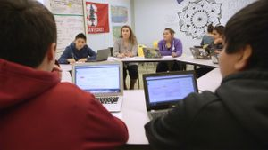 High school students are sitting in a circle made of trapezoidal desks at the center of the room, while another student works by herself, facing the wall.